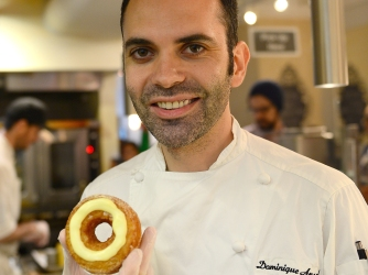 French pastry chef Dominique Ansel poses with a cronut, a croissant-doughnut hybrid, which he created, at his bakery shop in New York, June 14, 2013. Customers line up for hours before Ansel's shop opens in the morning to have a chance to buy two cronuts per person out of the 200 cronuts Ansel produces daily. The part flaky croissant, part cream-filled doughnut, the cronut, was introduced in mid-May and is retailing at $5 USD a piece. AFP PHOTO/Emmanuel Dunand (Photo credit should read EMMANUEL DUNAND/AFP/Getty Images)